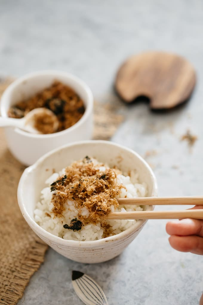 homemade katsuo soft rice seasoning is sprinkled over a bowl of rice and a pair of chopstick is scouping up
