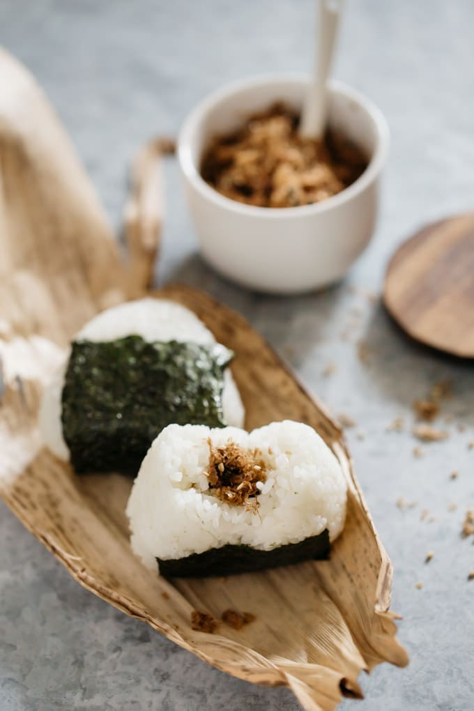 two onigiri rice balls with soft katsuo rice seasoning as filling on a bamboo leaf onigiri wrap