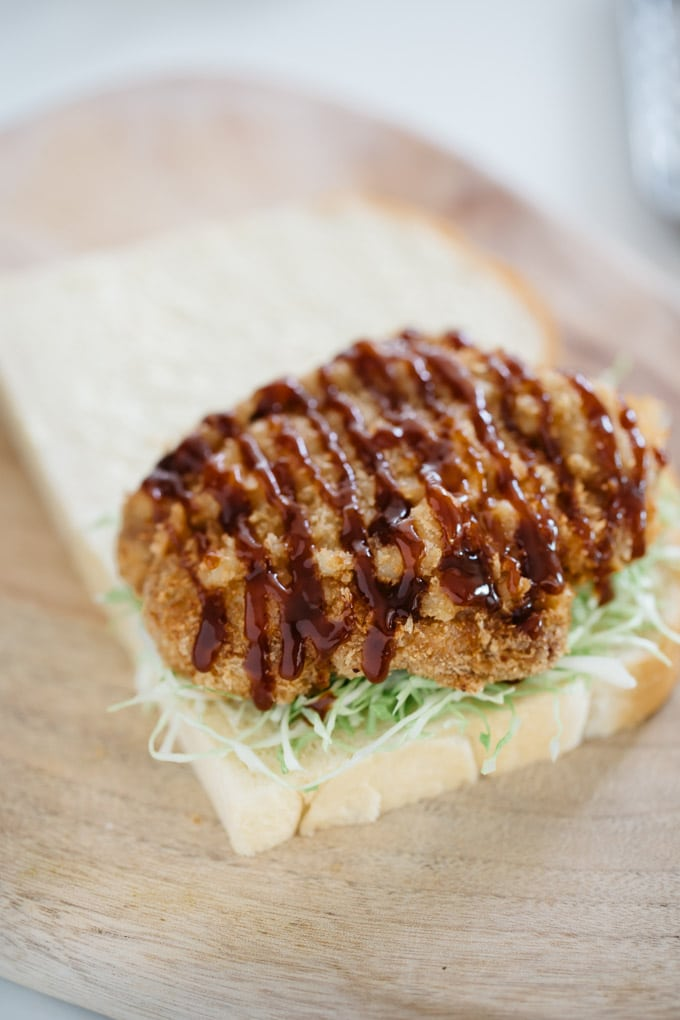 Two slices of Shokupan bread on a chopping board. One with shredded cabbage and Katsu on top of it. Tonkatsu sauce drizzling.