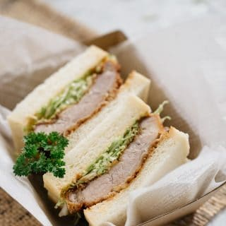 Two slices of Katsu Sando in a cardboard takeaway container