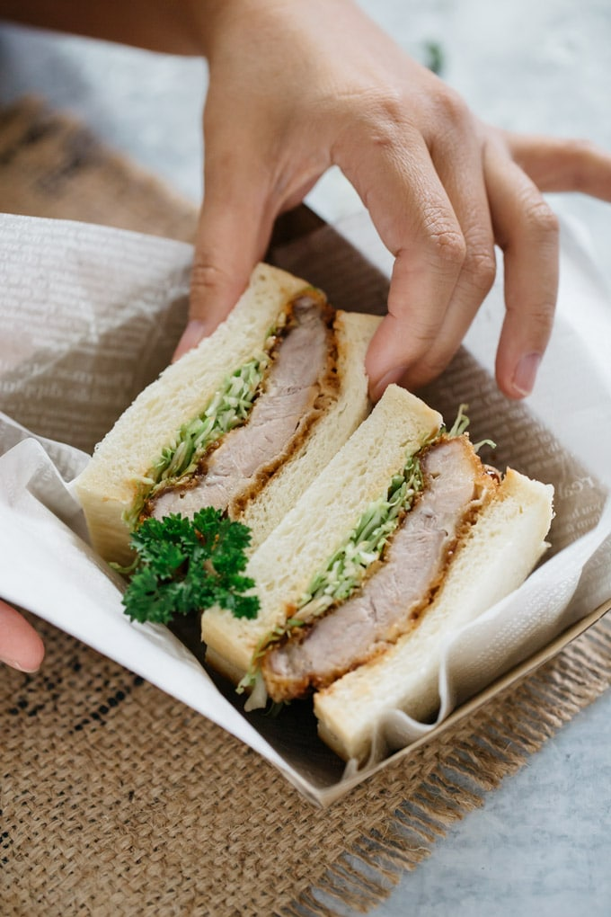 two slices of Katsu sando in a cardboard takeaway container and a hand picking one sandwich