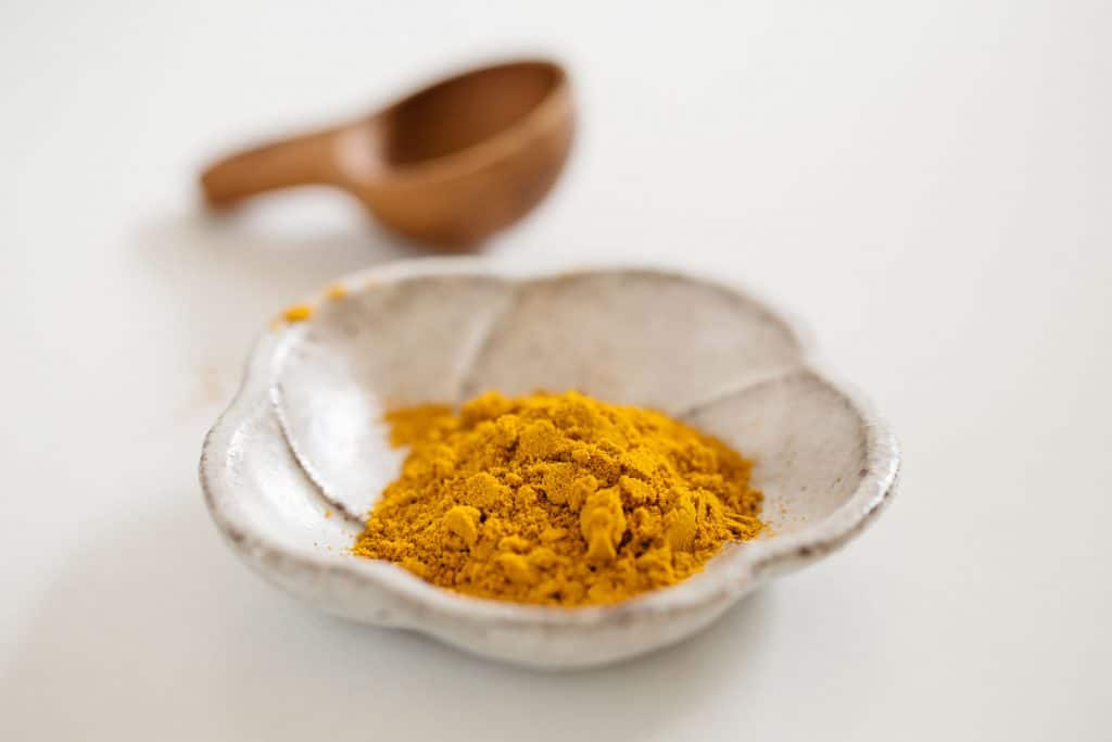 Turmeric in a small bowl with a wooden tea spoon