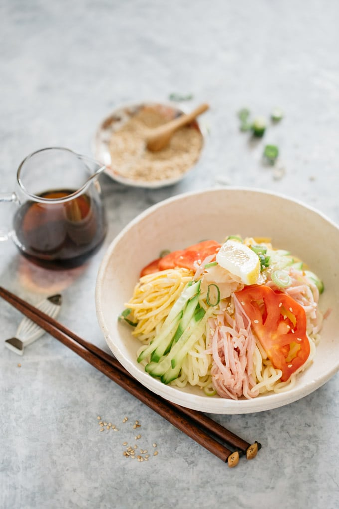 A bowl of hiyashi chuka, a small jug of sauce and sesame seeds small bowl