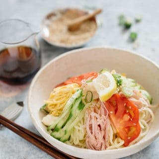 Hiyashi chuka served in a white shallow bowl and a small jar of dipping sauce and a pair of chopstick