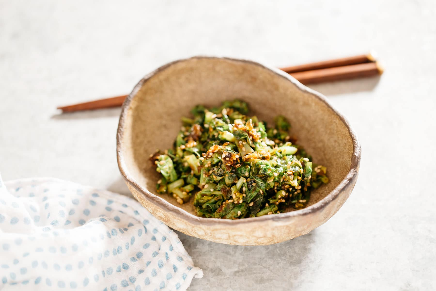white radish leaves stir fry served in an oval bowl with a pair of chopstick