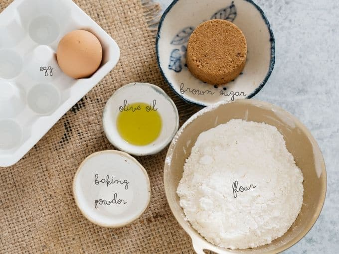 brown sugar in a small bowl, one egg, olive oil, flour and baking powder in separate bowls