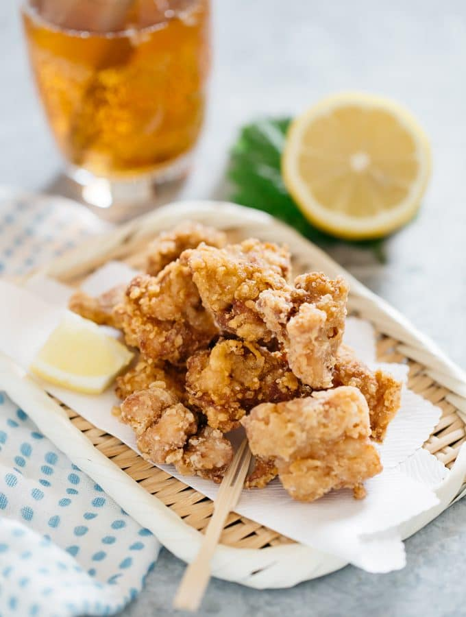Karaage served on a bamboo tray with drink in the background with half lemon