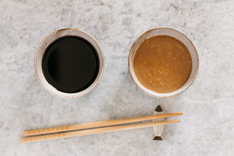 Sweet Soy sauce (left) and sesame (right) dipping sauce in small bowls