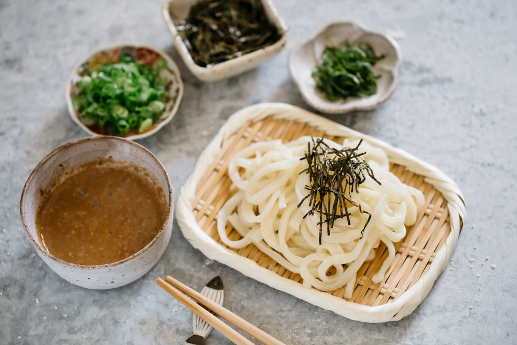 Udon noodles served on a bamboo tray with a small bowl of dipping sauce and yakumi