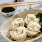 four rose dumplings served on a oval plate with a small bowl of dippping sauce and a pair of chopstick