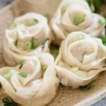 four rose dumplings served on an oval plate with a pair of chopstick on a small bowl of dipping sauce in background
