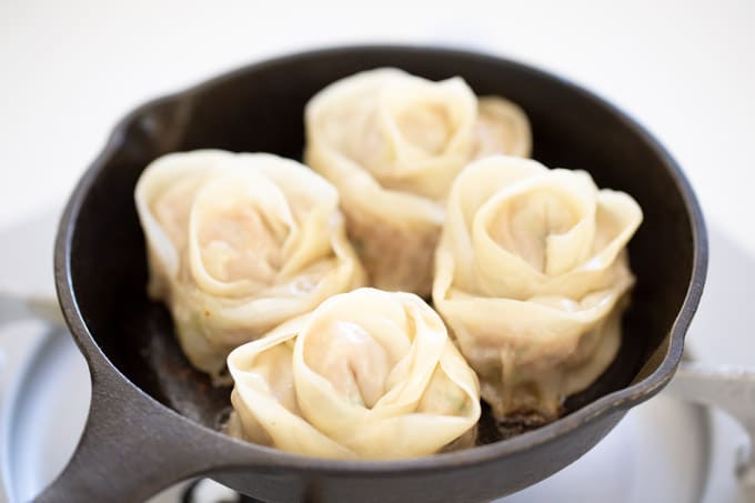 four rose dumplings in a skillet
