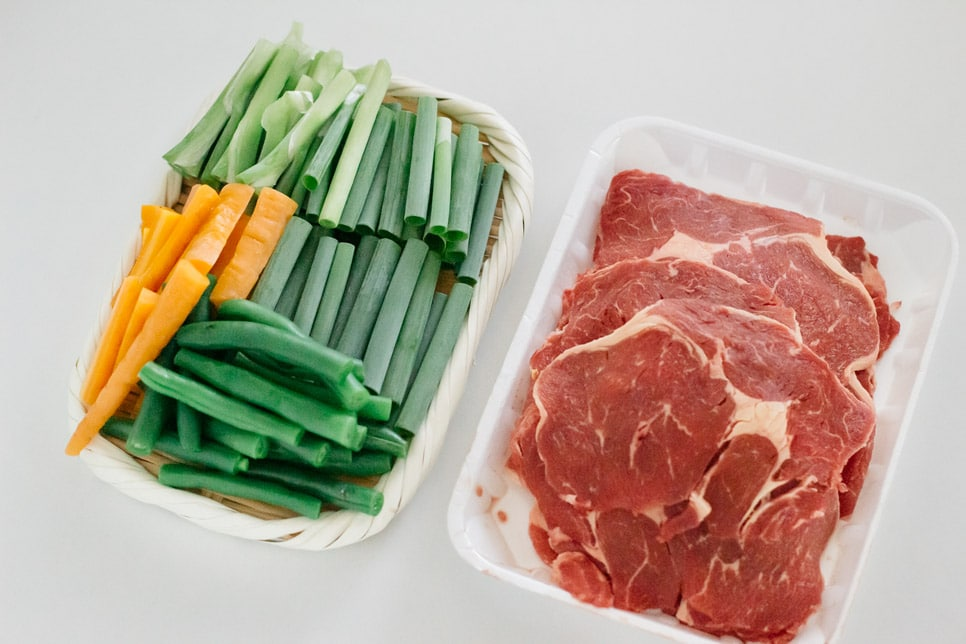 thinly sliced beef on the right and scallions cooked carrot and green beans on the left