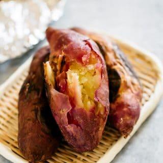Three roasted sweet potatoes on a bamboo tray