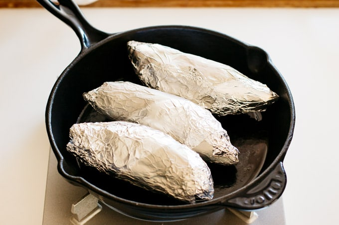 three sweet potatoes wrapped with aluminium foil in a skillet