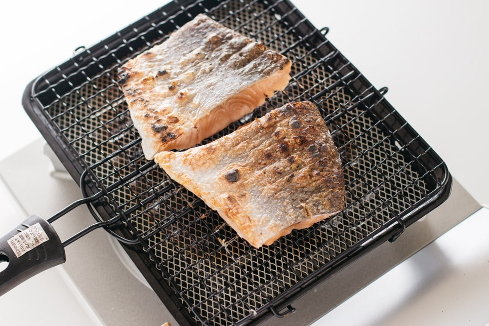 two pieces of shiozake being grilled over a grill