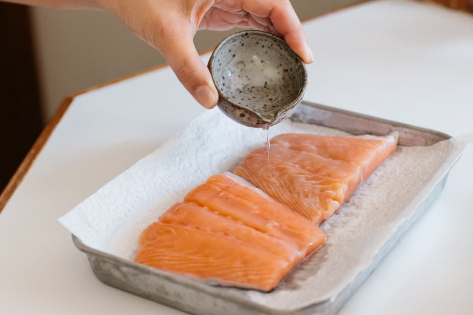 sprinkling sake over two pieces of fresh salmon