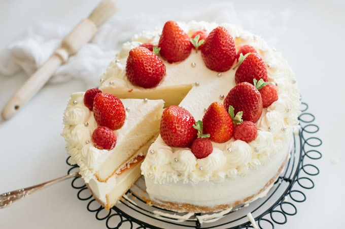 a whole strawberry shortcake cake and a piece of it coming out on a cake server