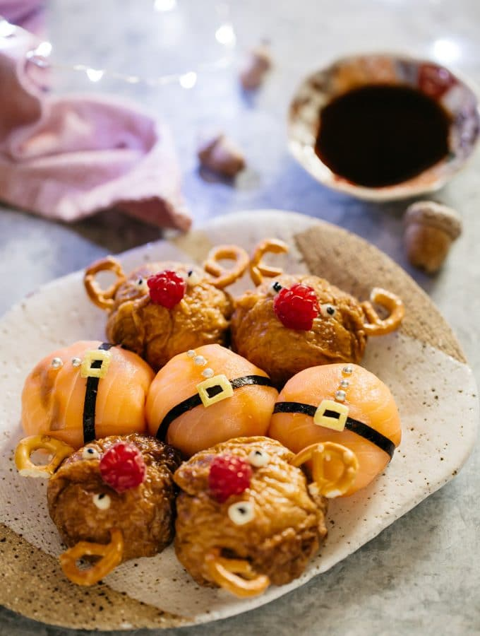 four reindeer rice balls and santa rice balls on a plate