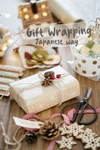 a box neatly wrapped with natural coloured wrapping paper with natural objects and other materials need for wrapping around it.