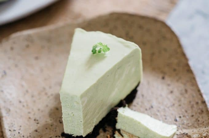 A piece of no bake cheesecake matcha oreo crust served on a square plate with a bamboo folk
