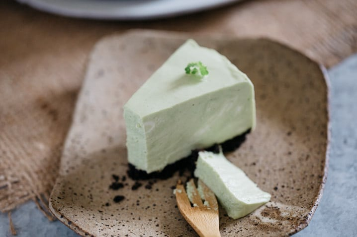 a piece of no bake cheesecake matcha mabled on a plate