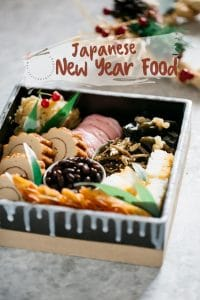 """Japanese new years food """"Osechi ryori"""" dishes served in a square Japanese pottery."""
