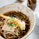 Toshikoshi soba noodle served in a noodle bowl with a tempura prawn and kamaboko fish cake with soup