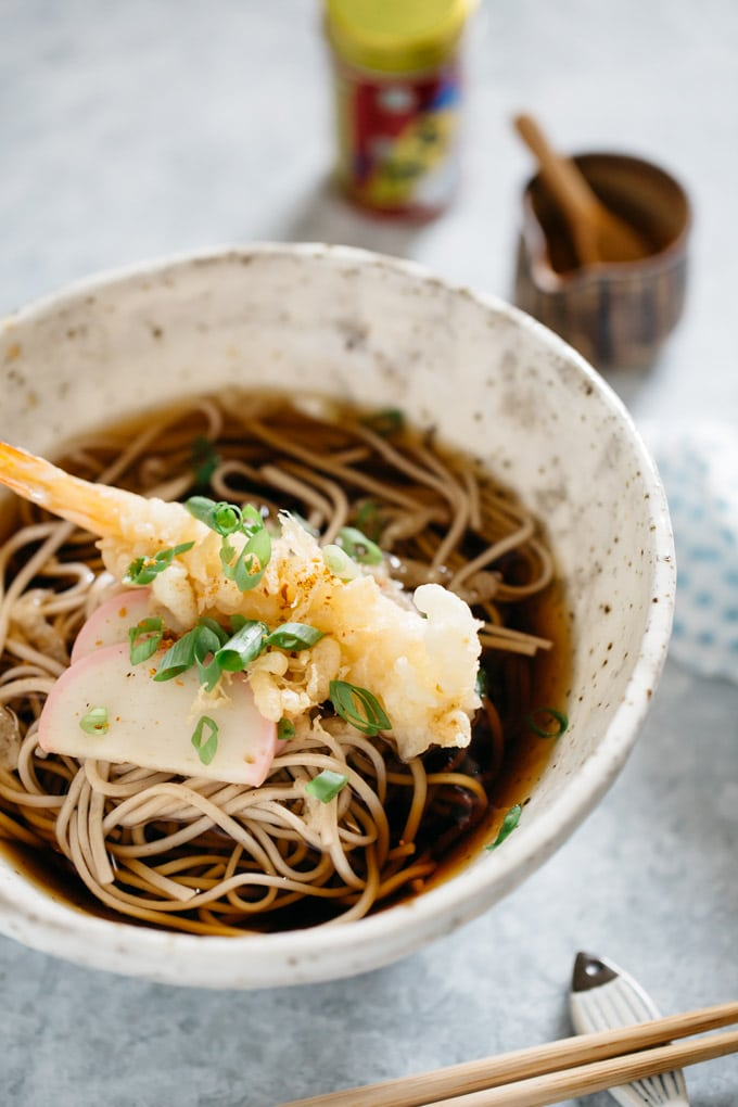 Toshikoshi soba served in a noodle bowl with a prawn tempura, two kamaboko fish cakes and soup