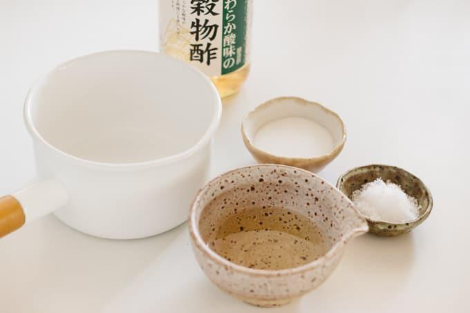 rice vinegar bottle, rice vinegar in a small bowl, sugar in a small bowl, and salt in a small bowl