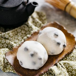 Two daifuku served on a rectangle shaped plate with a black steel teapot and a bamboo whisk.