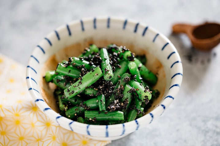 Green beans goma ae served in a small Japanese mortar.