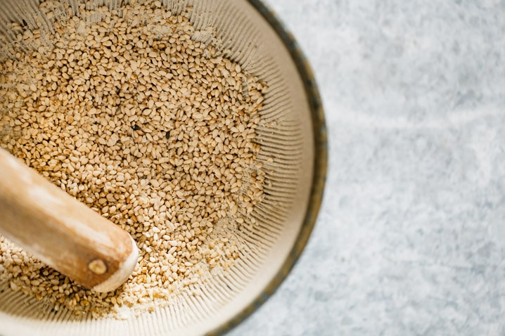 white sesame seeds in a japanese mortar with an wooden pestle