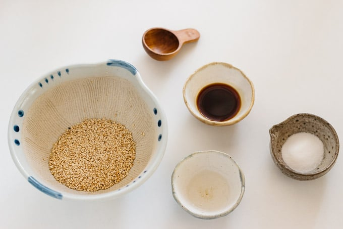 white sesame seeds in a Japanese mortar, soy sauce, dashi, and sugar in small bowls