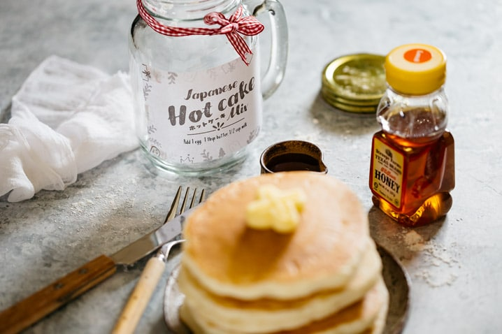 Japanese hot cake mix jar in back ground and 4 pancakes on a round plate stacked up with butter on top