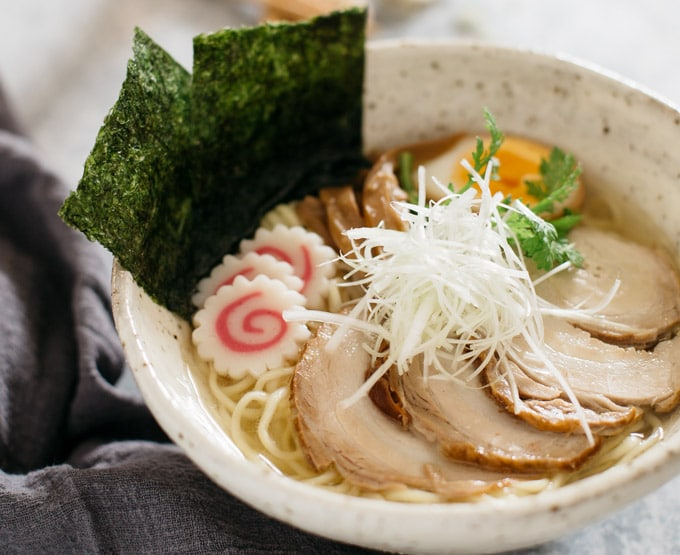 shio ramen topped with three slices of chashu and naruto and two large piece of nori sheet and chopped scallions