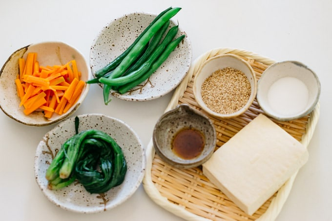 parboiled carrot, green beans, spinach on a shallow bowl, tofu drained, sesame seeds, sugar, soy sauce on a bamboo tray