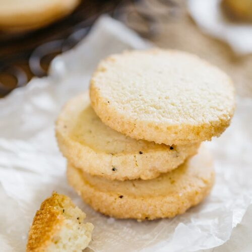Three butter cookie stacked on a round plate with some crumbs
