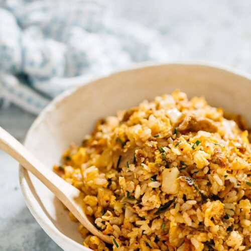 kimchi fried rice served in a shallow round bowl with a bamboo spoon