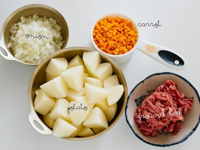 peeled and chopped potato, carrot, onion in bowls and ground beef