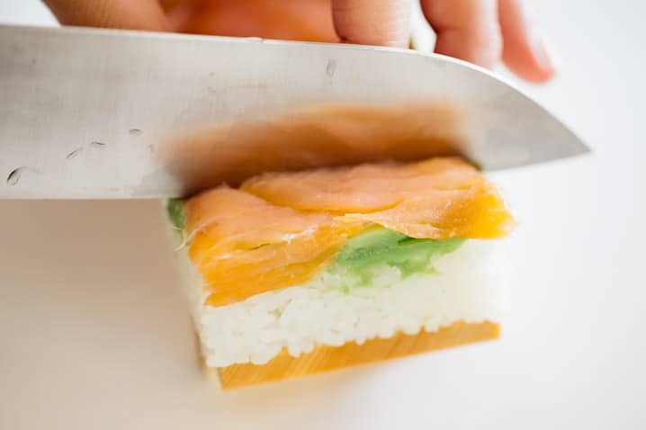 cutting pressed salmon sushi with a sharp knife