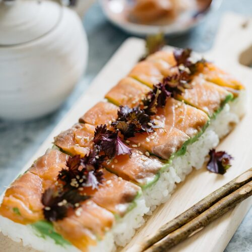 smoked salmon pressed sushi is cut and served on a wooden serving board