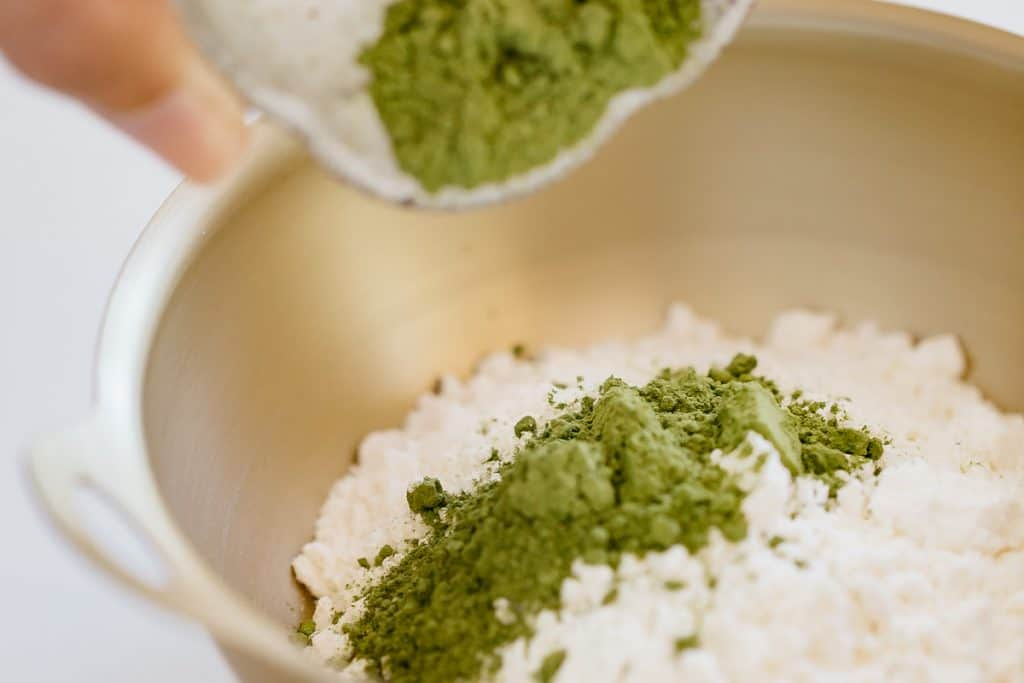 Matcha powder added to a bowl of flour