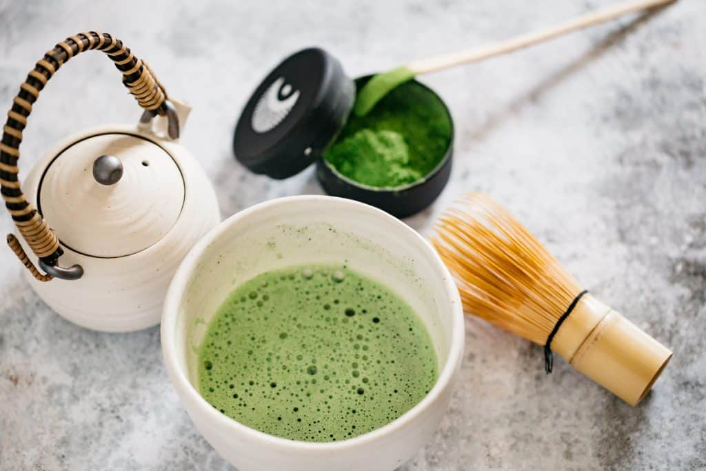 Matcha green tea served in a tea bowl with matcha container with matcha in it and a bamboo whisk