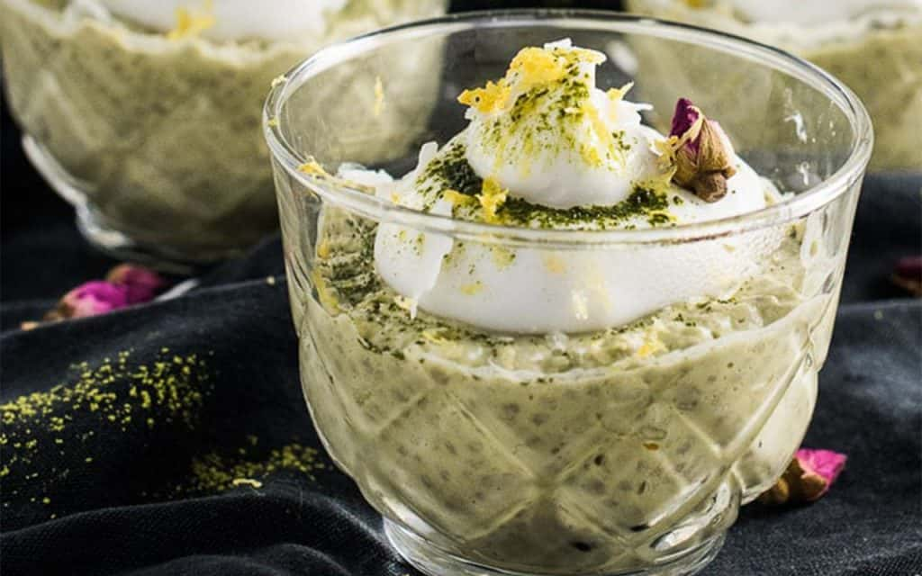 Coconut lemon chia matcha pudding served in a glass with lemon zest