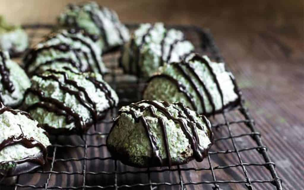 coconut matcha macaroons on a black wire  rack