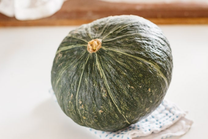 a whole kabocha squash on kitchen bench