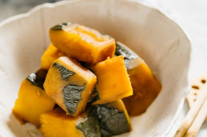 simmered Kabocha squash served in a Japanese pottery serving bowl with a pair of chopstick