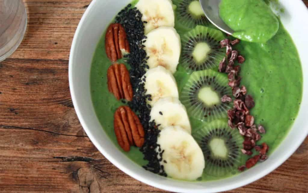 Matcha smoothie served with slice of banana and kiwis with a spoon