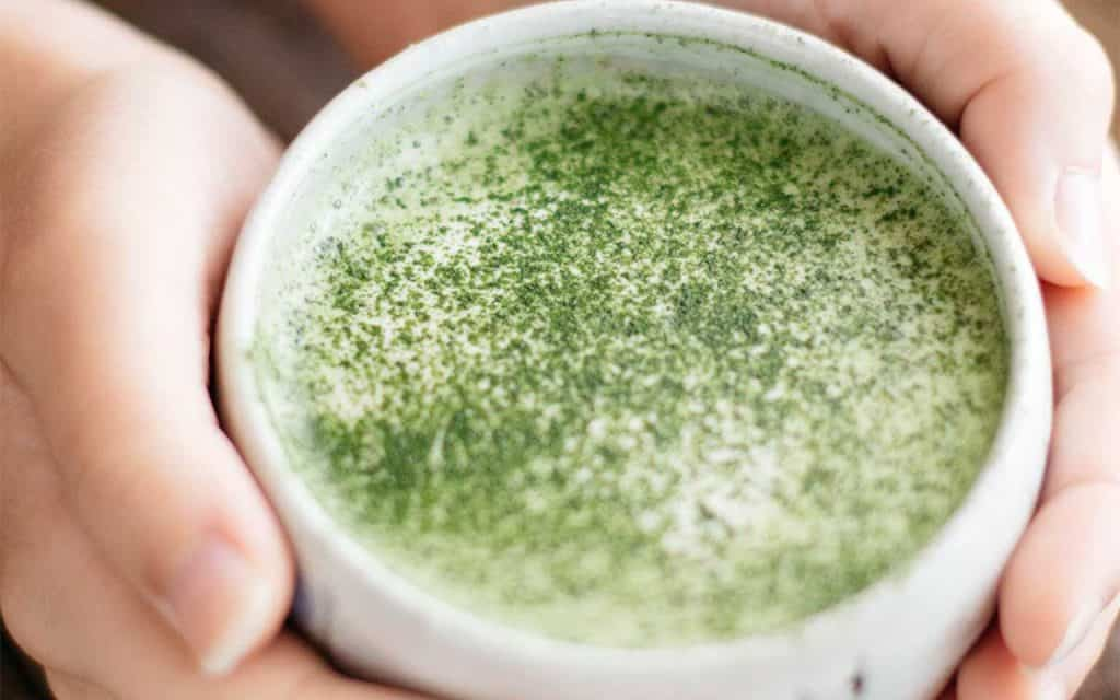 matcha latte served in a small cafe bowl two hands holding the bowl